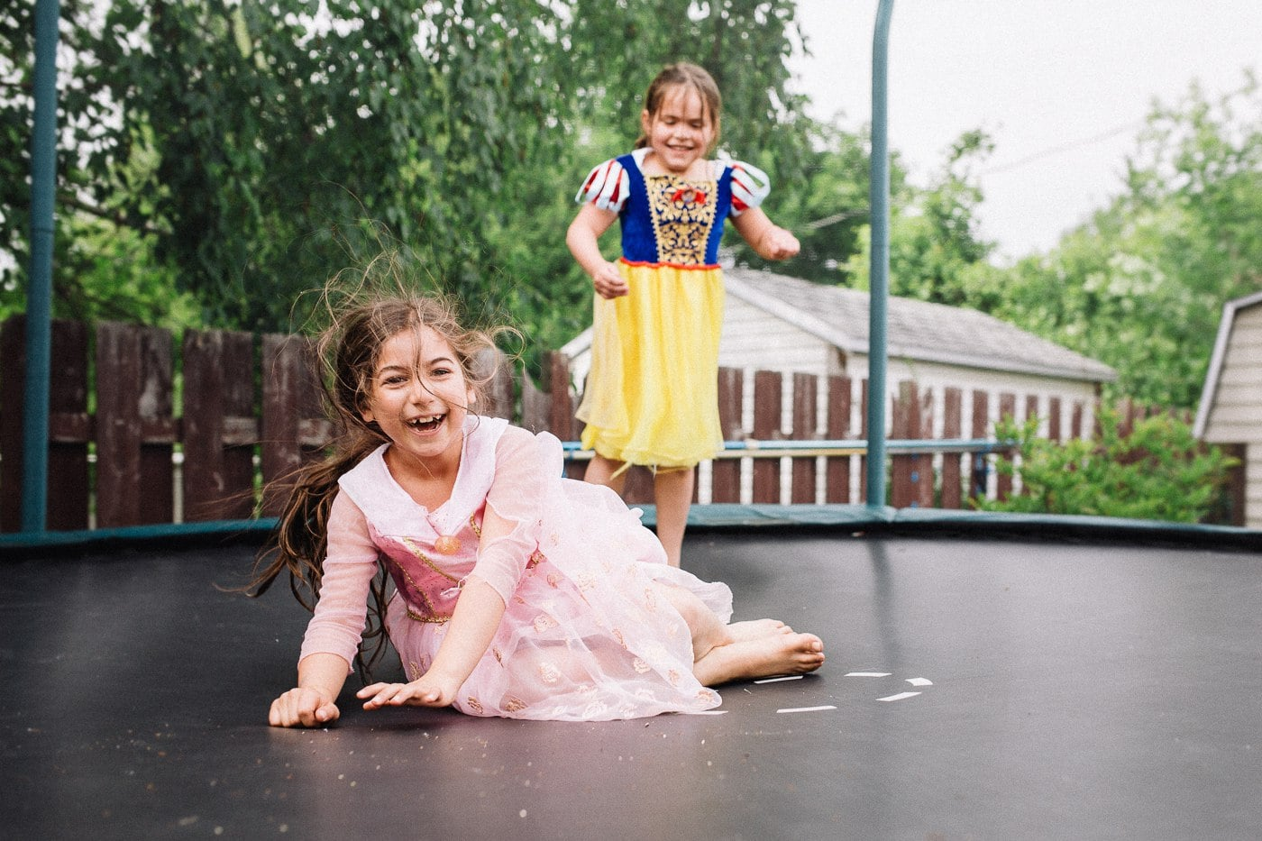 girls on trampoline in princess dresses laughing