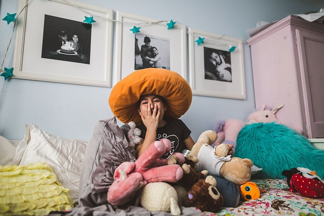 girl laughing on bed surrounded by stuffed animals carolina hanna montreal family photography