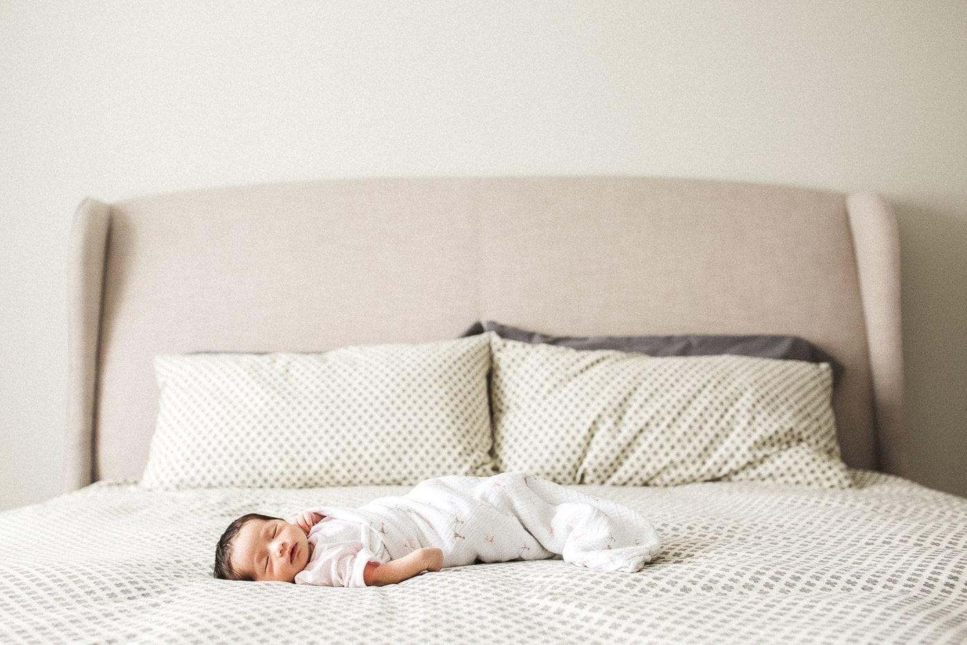 newborn girl sleeping on parents bed montreal newborn baby photographer