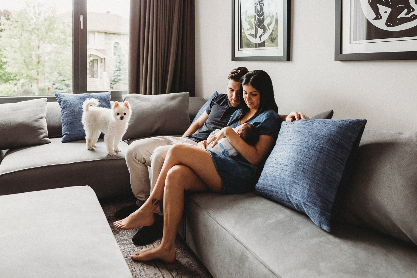 parents on sofa holding newborn baby as dog watches on montreal photographer