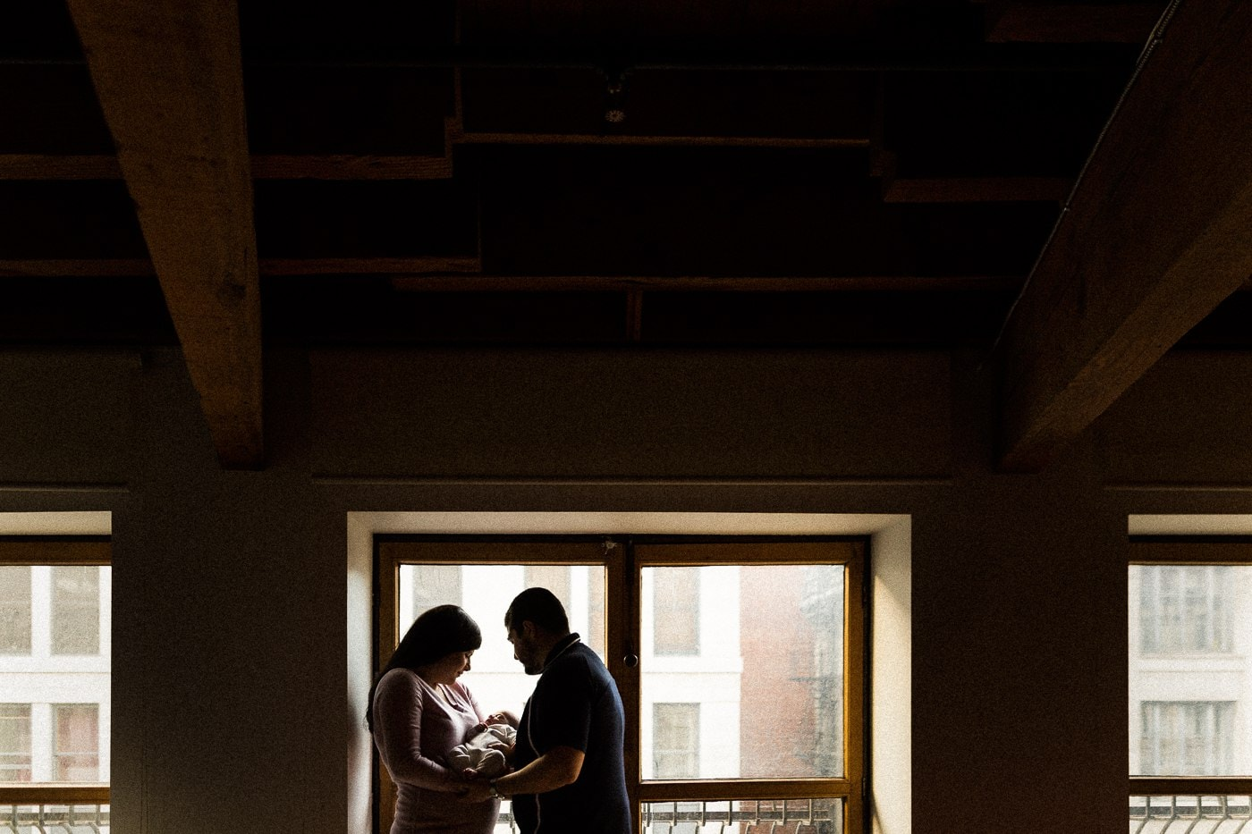 silhouette parents holding baby by window