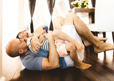 dad and boy laughing on floor