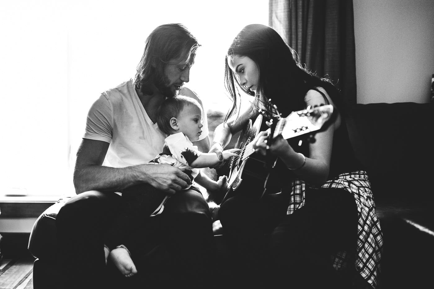 parents playing guitar to baby