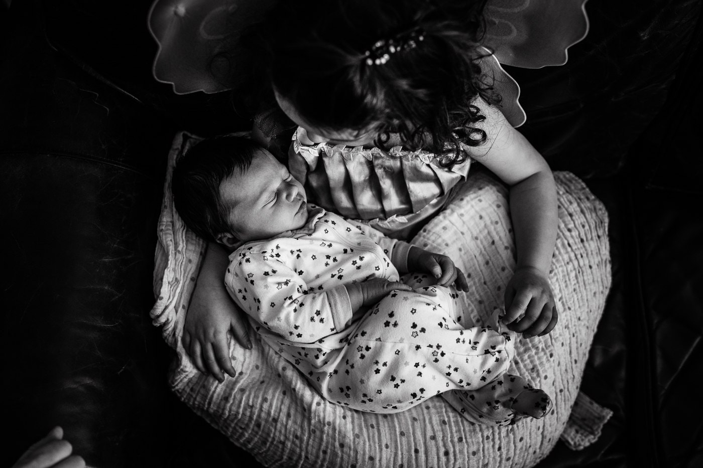 toddler girl holding newborn brother photography