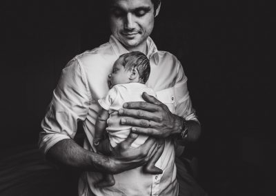 newborn in dad's arms black and white photograph
