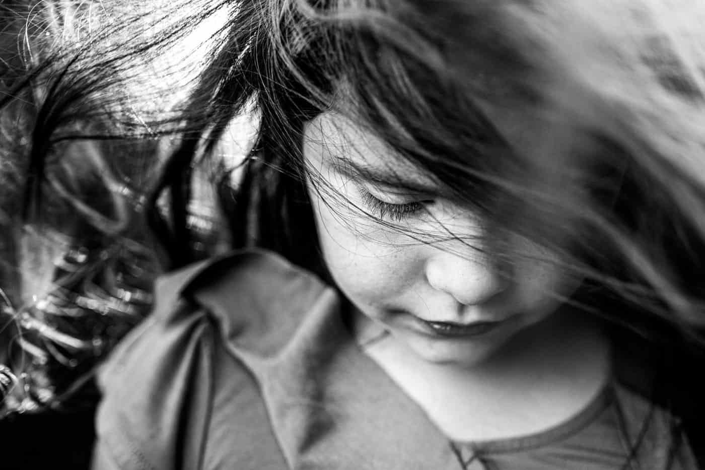 Close up of young girl with her hair blowing in the wind