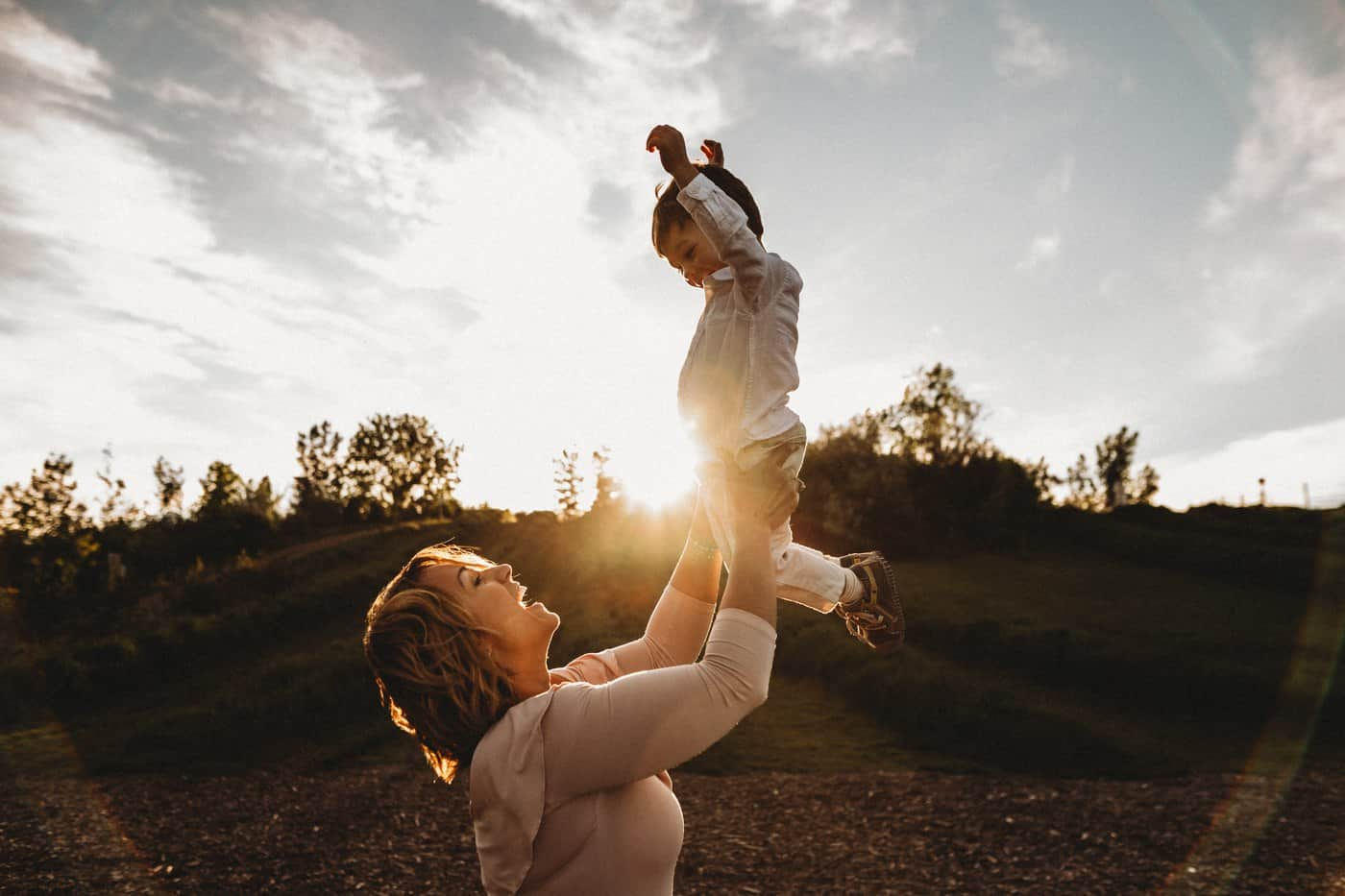 Mother and son outside at sunset, swinging little boy in the air and laughing