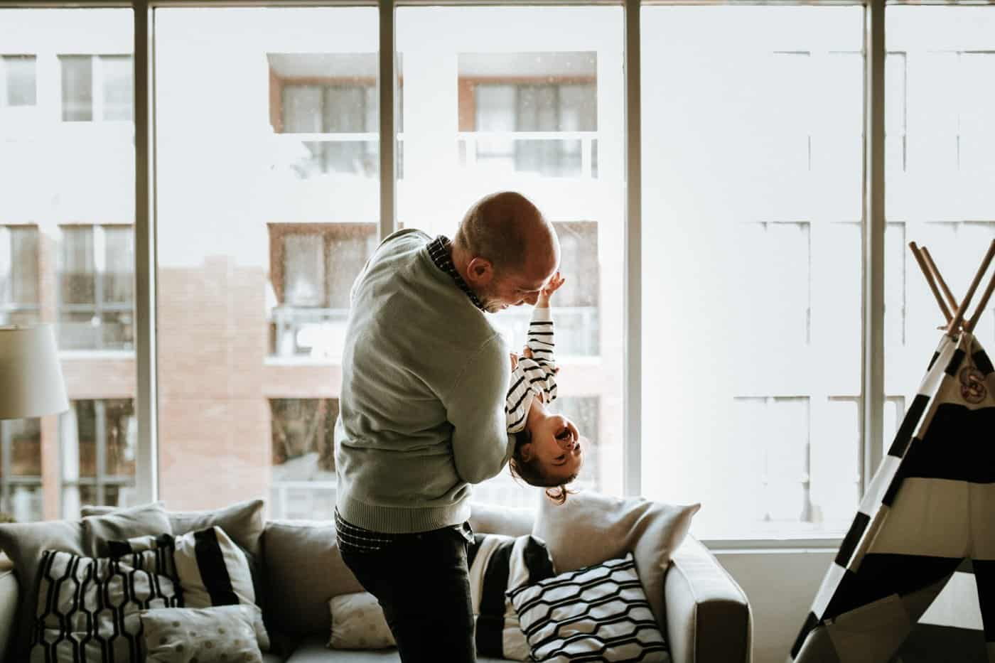 man playing with son in their home