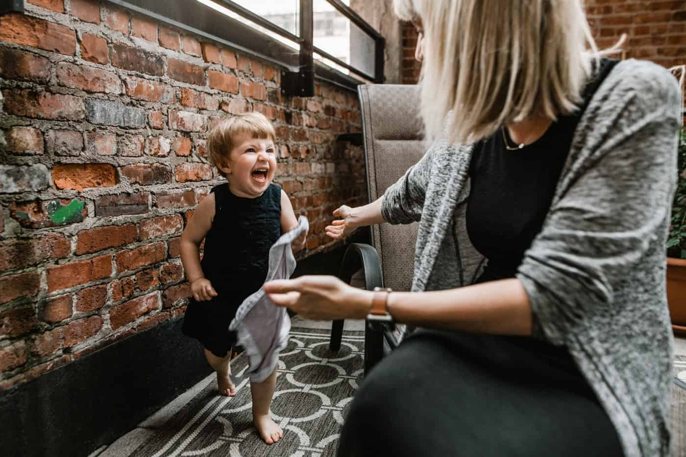 Young girl running towards mom laughing