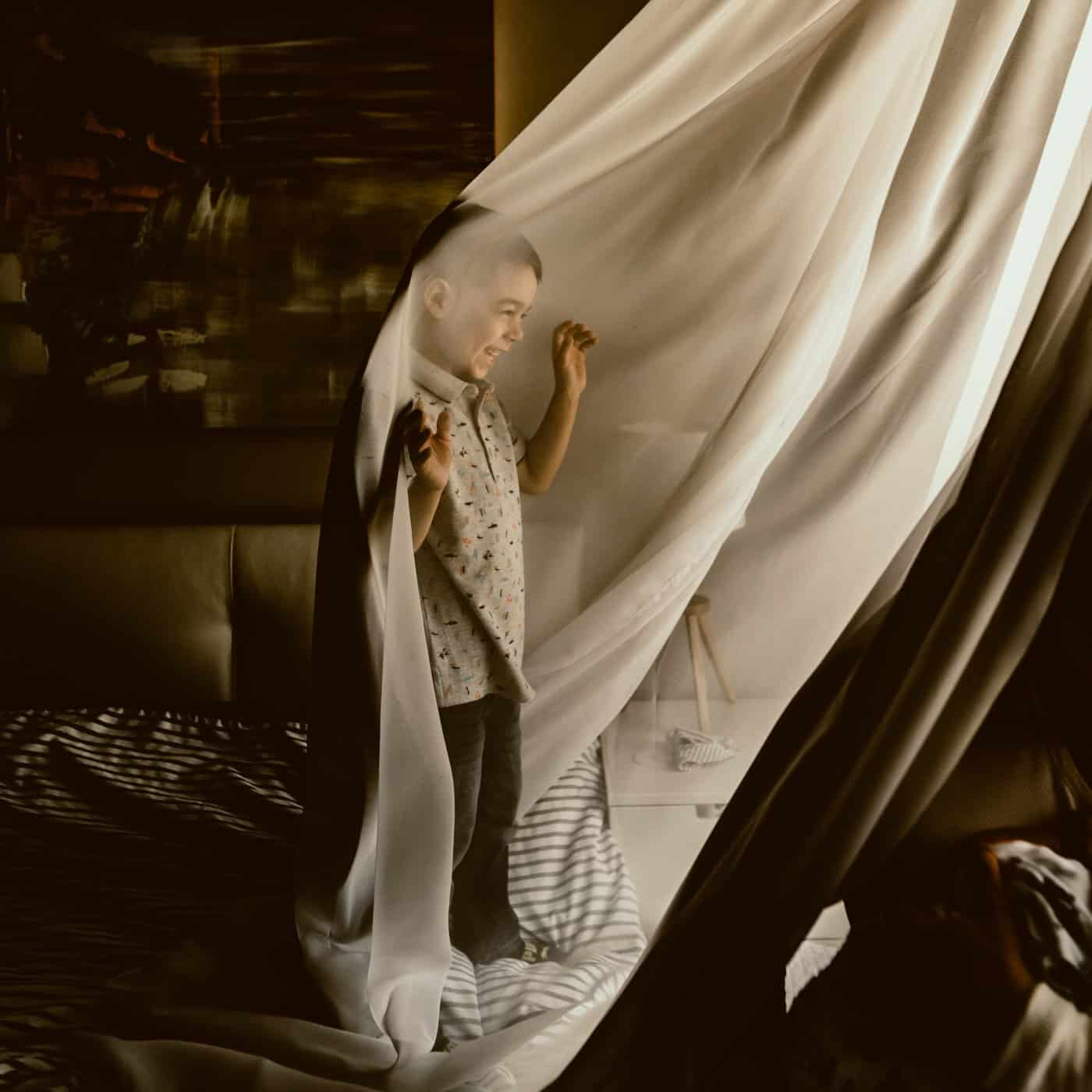 Young boy playing in sheer curtains