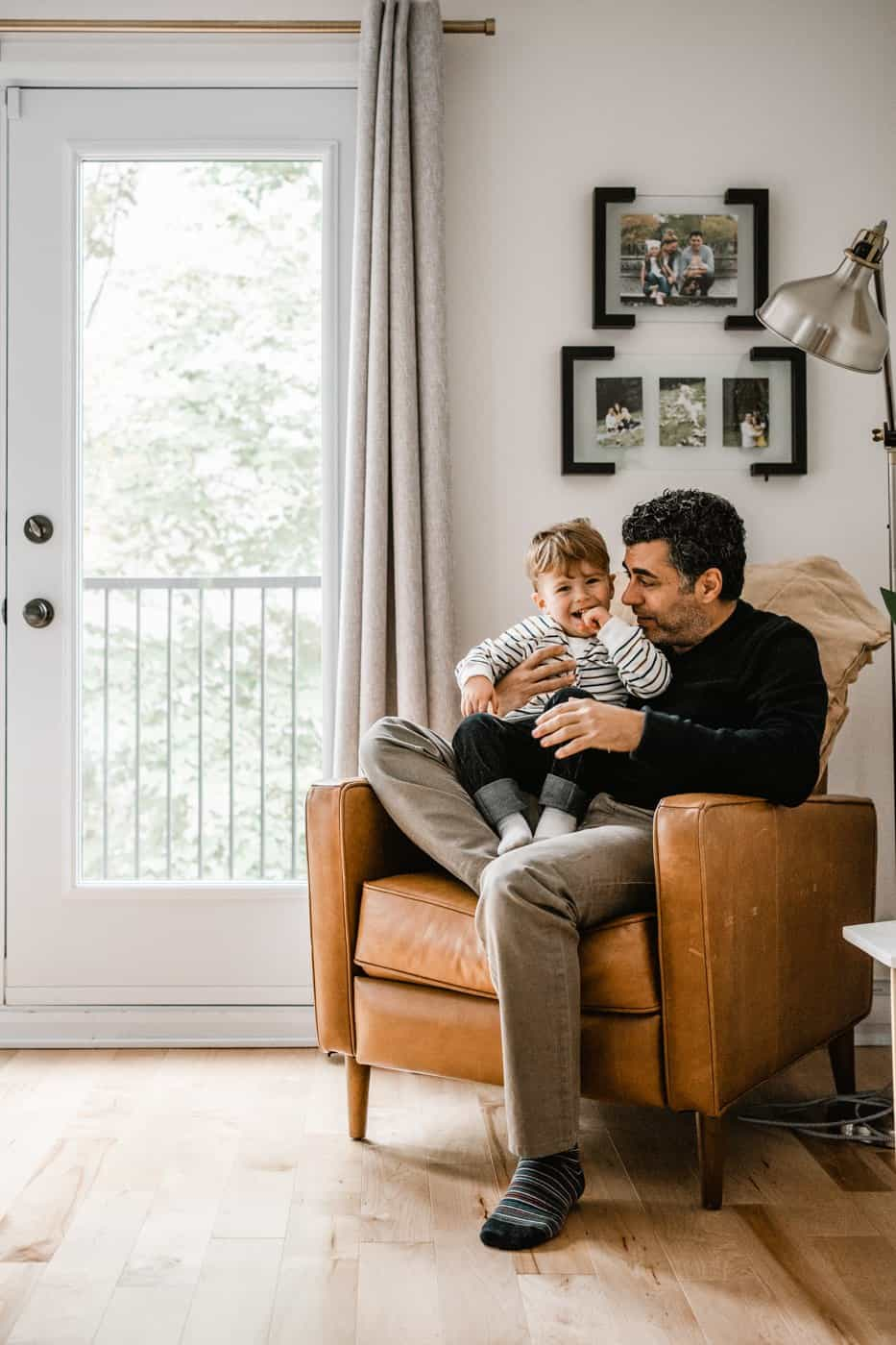 Man and son sitting on brown leather chair