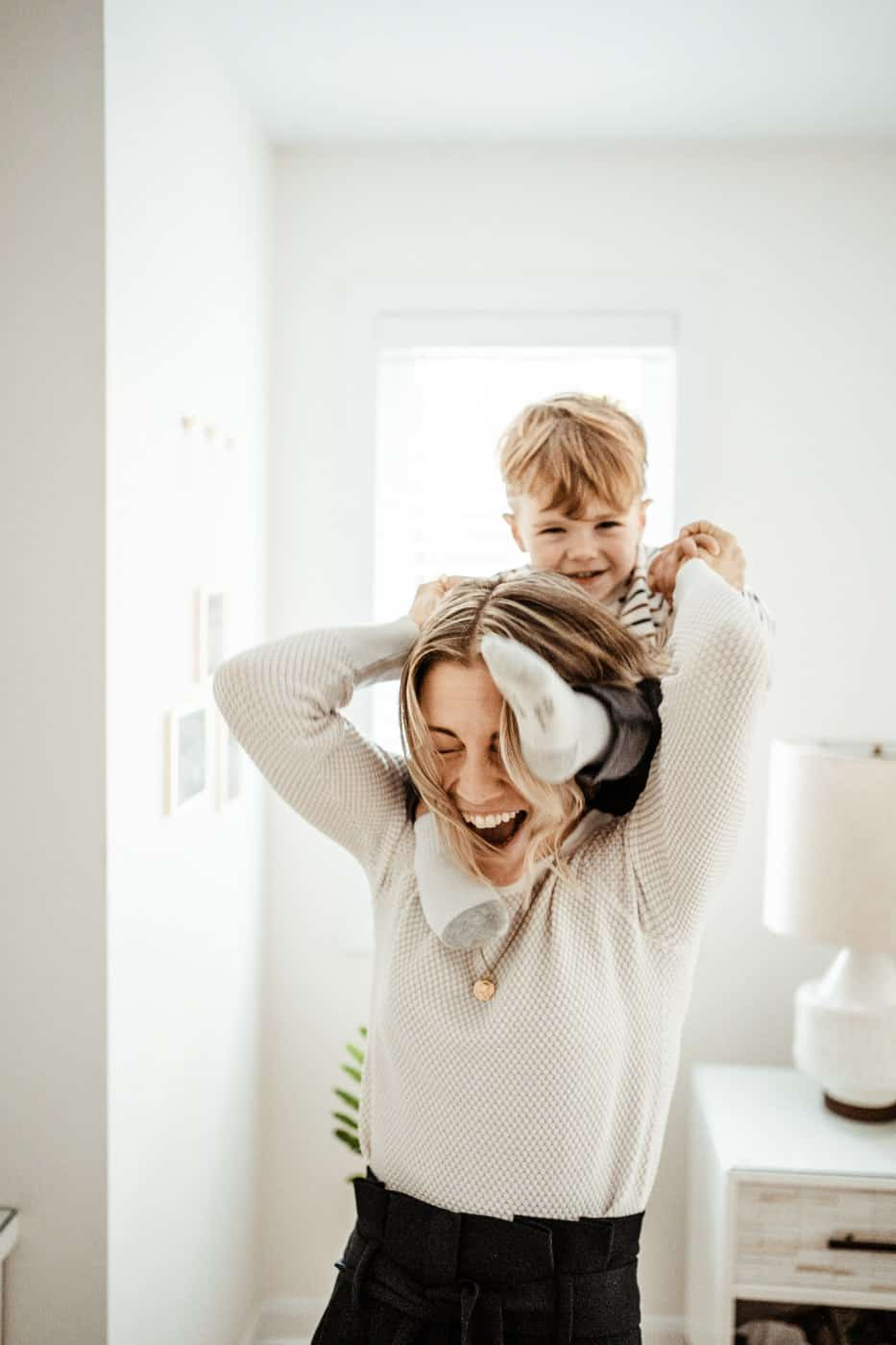 woman laughing with son on shoulders