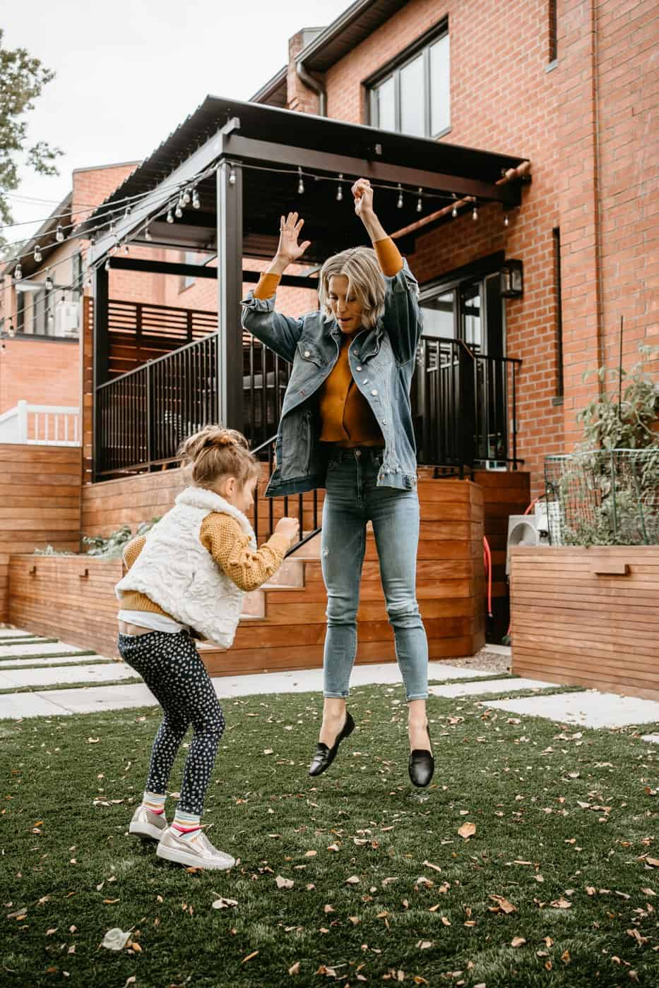 Mom and daughter jumping in backyard