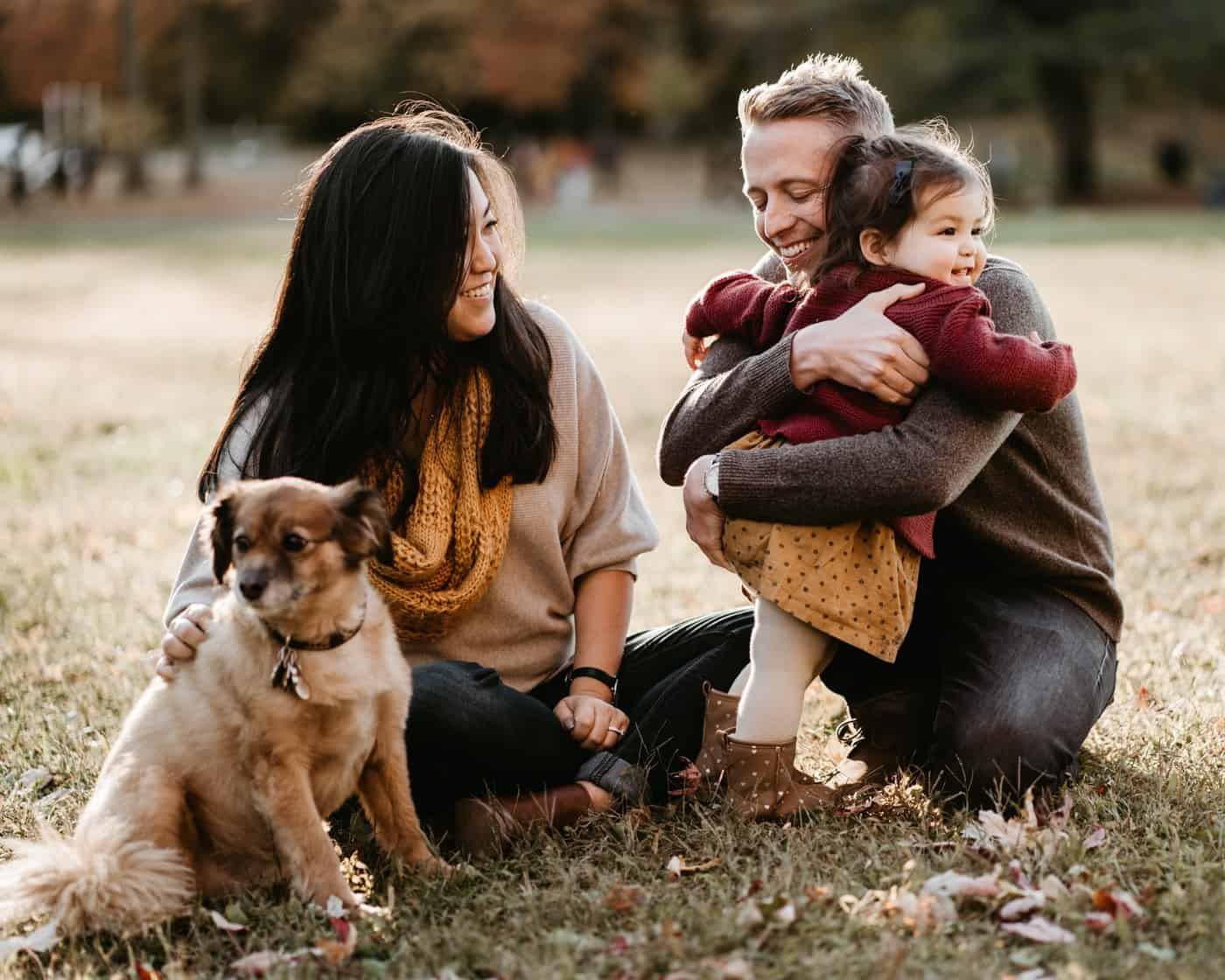 Mom, dad, little girl and their dog outside as girl hugs dad