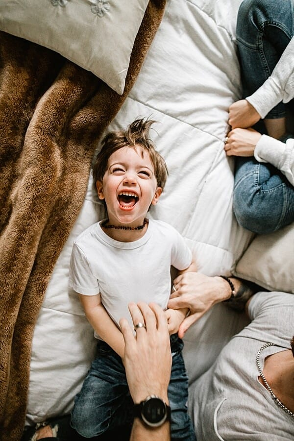 Young boy lying on bed in white shirt laughing as dad tickles him
