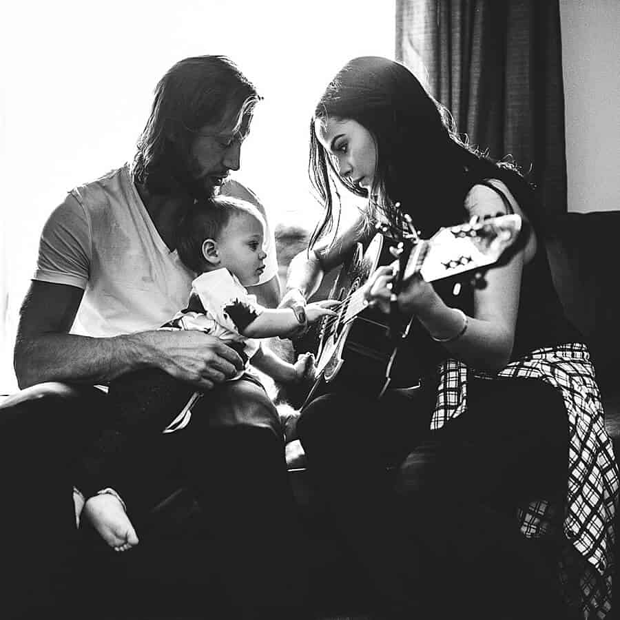 mom dad and toddler playing guitare together at home