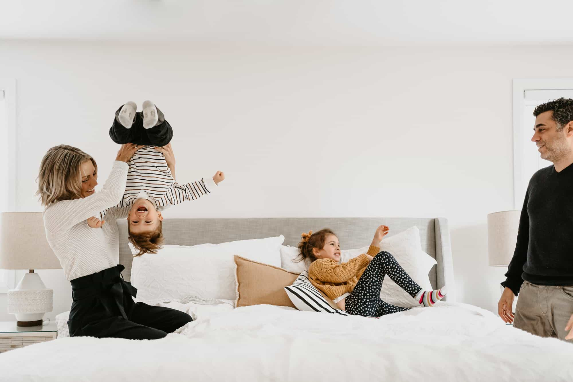 Family on bed playing with children