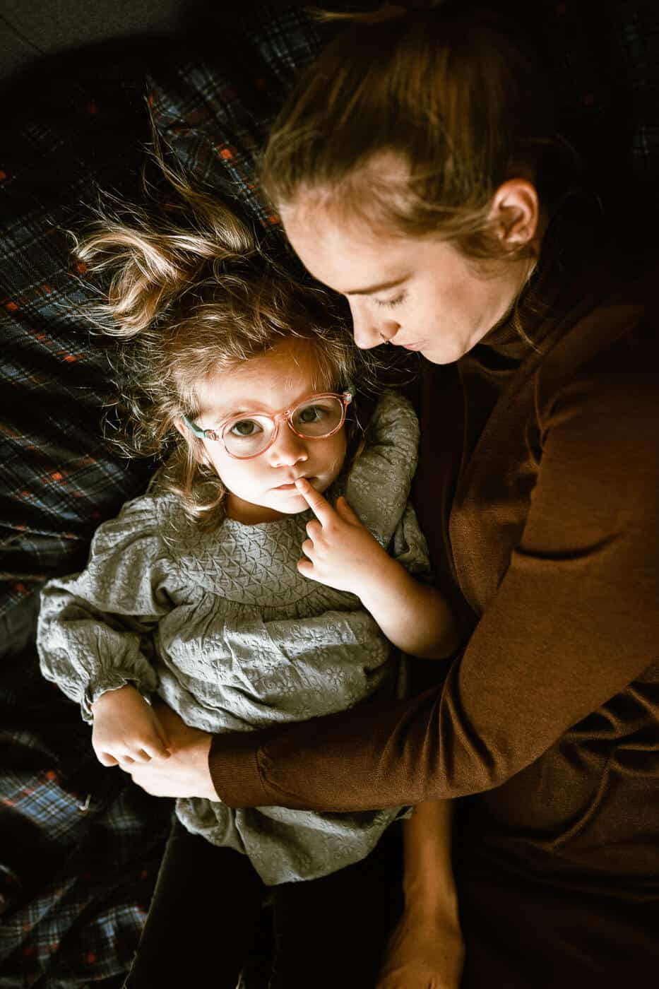 Little girl lying on bed with mom looking at camera