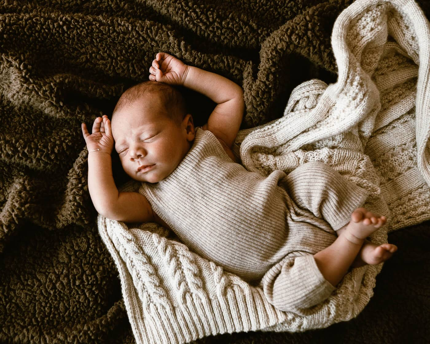 Newborn baby wearing beige onepice jumpsuit on knit blanket on bed
