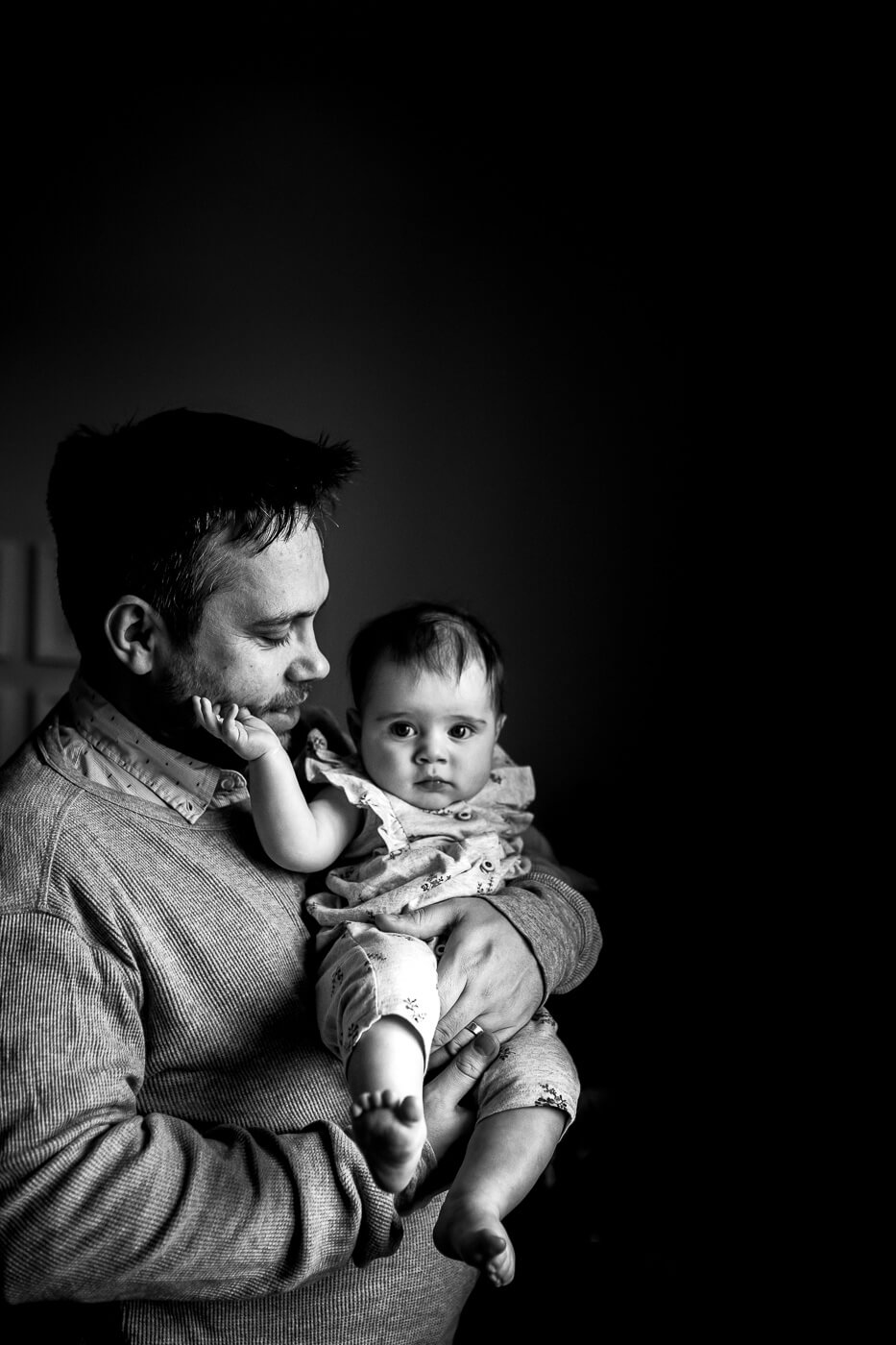 Baby girl in dad's arms with her hand on his cheek in black & white