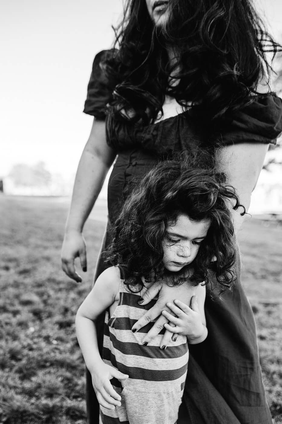 Black & white portrait of mom and son with long hair blowing in the wind and her hand on his chest