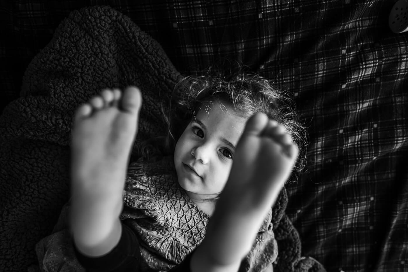 Black & White photo of little girl with her feet up in the air