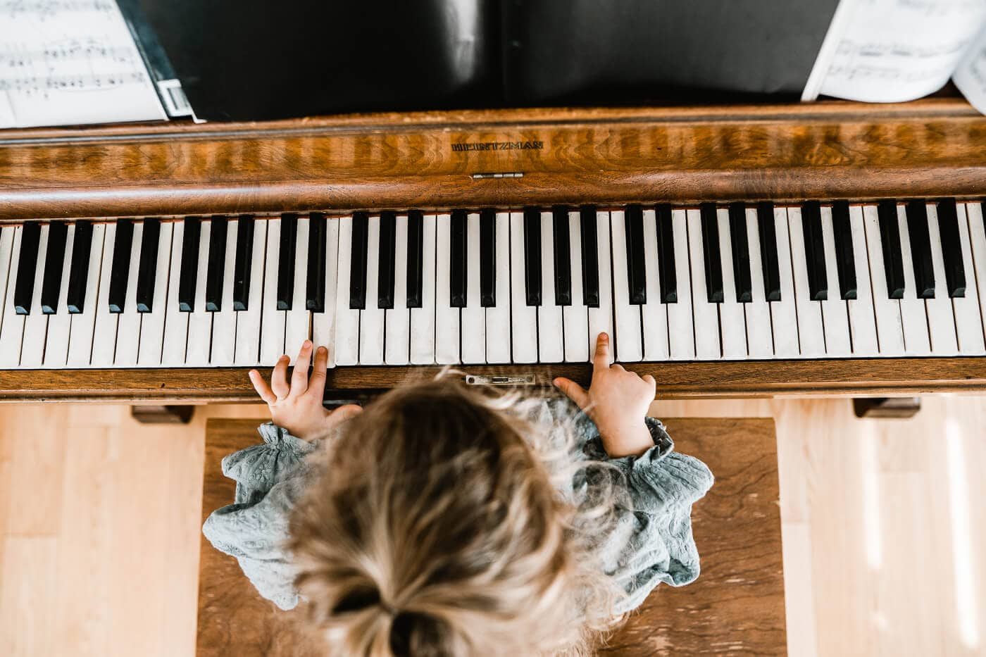 Bird's eye view of little girl's hands playing piano