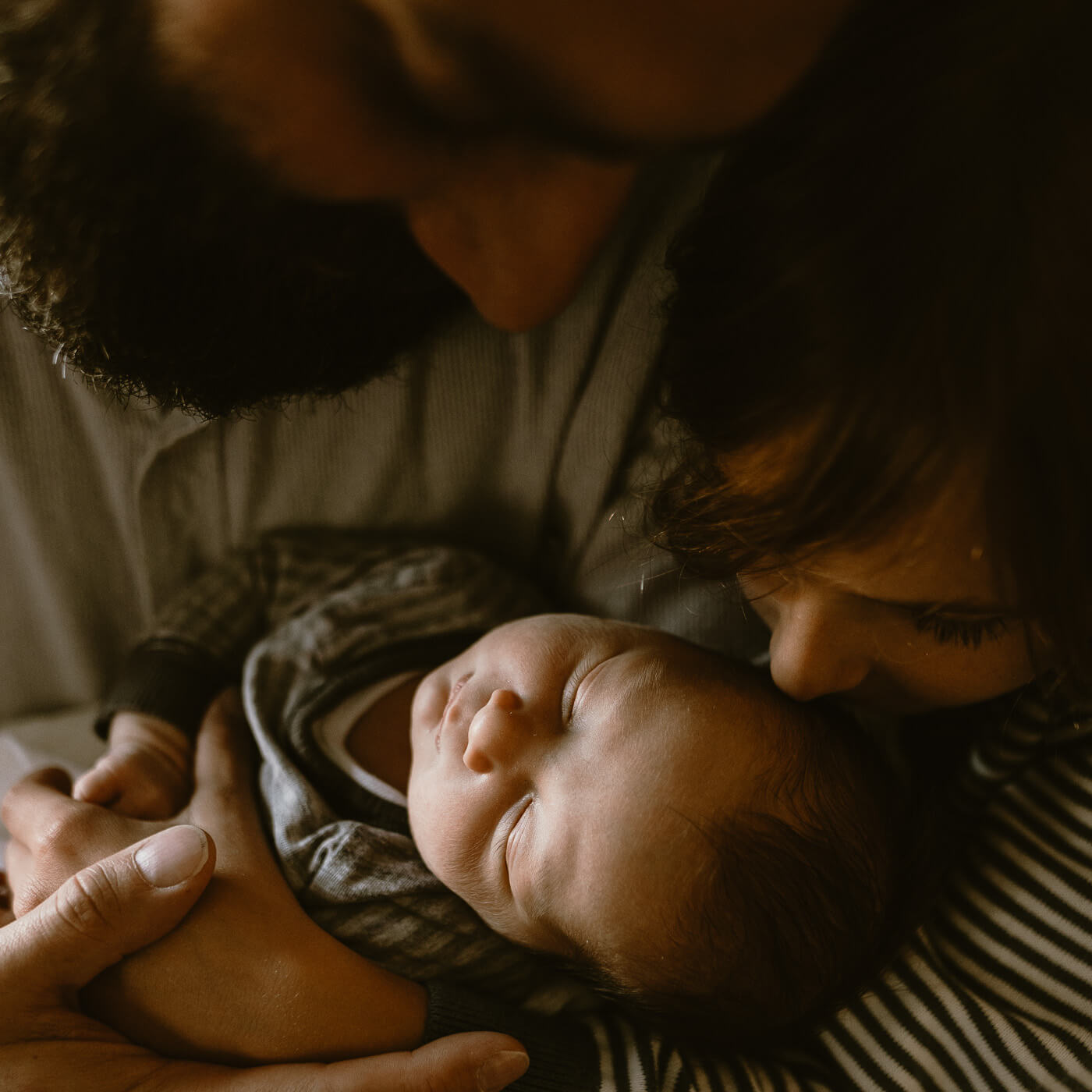 Close up of dad and big brother snuggling newborn baby