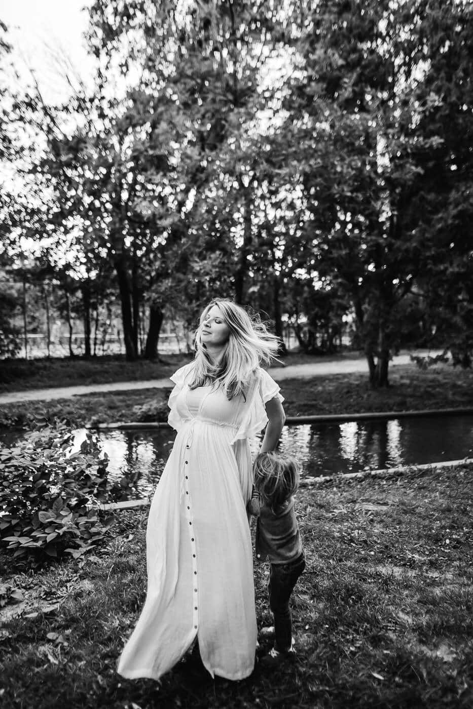 Pregnant mom with wind blowing through her hair as young son runs around her