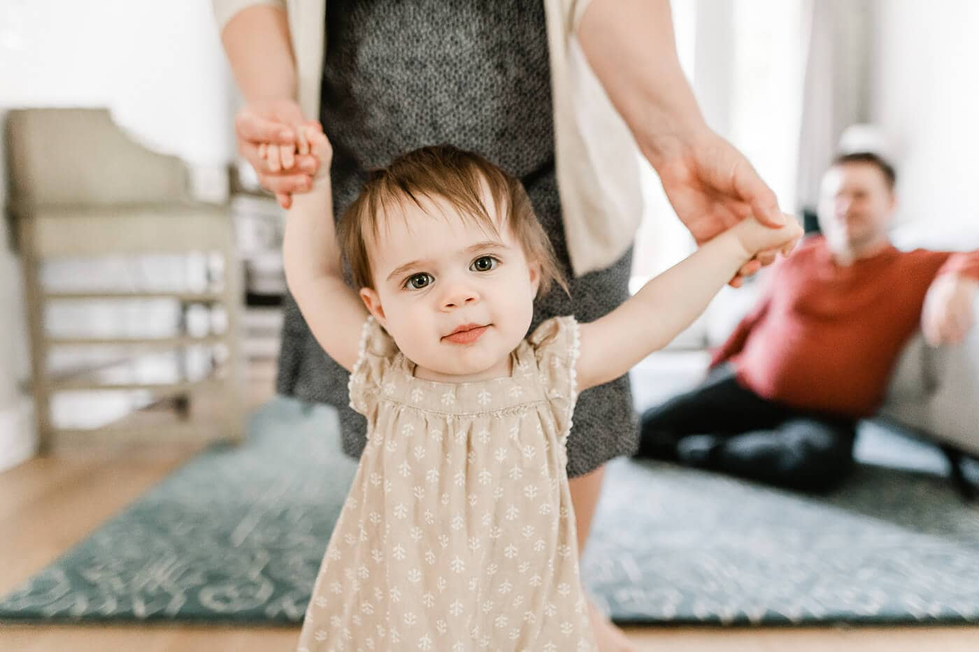 Baby girl learning to walk holding mom's hands