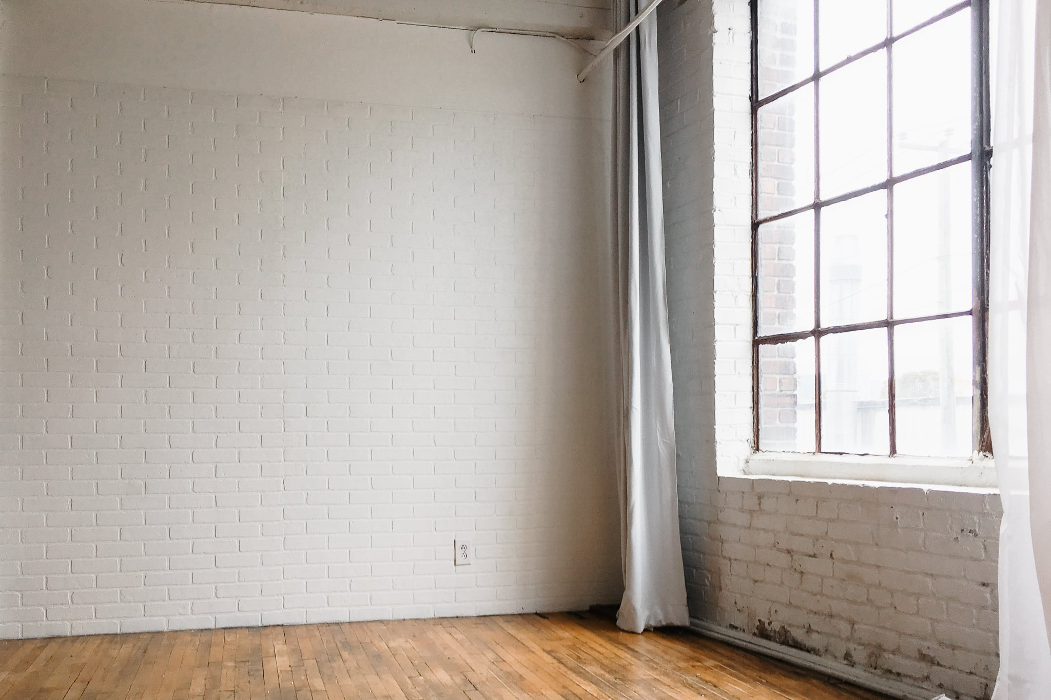 empty studio with white brick walls and large windows, in montreal