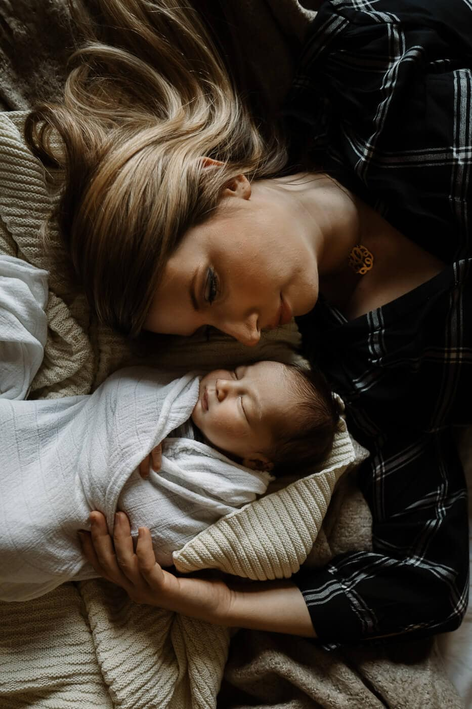 blond woman lying on bed with newborn baby boy in hampstead montreal